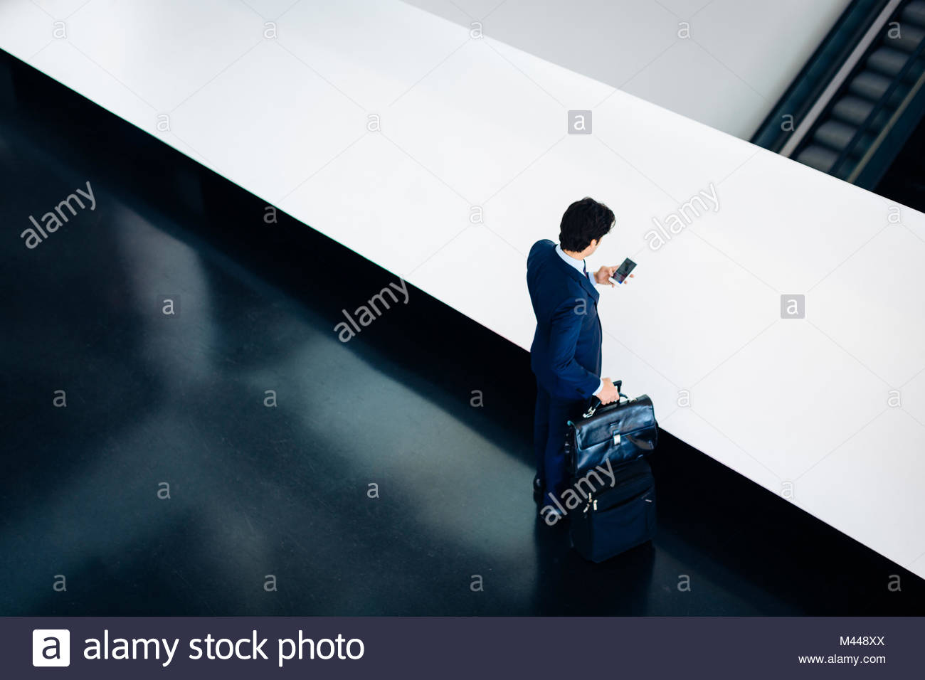 Businessman with wheeled luggage in hotel building - Stock Image