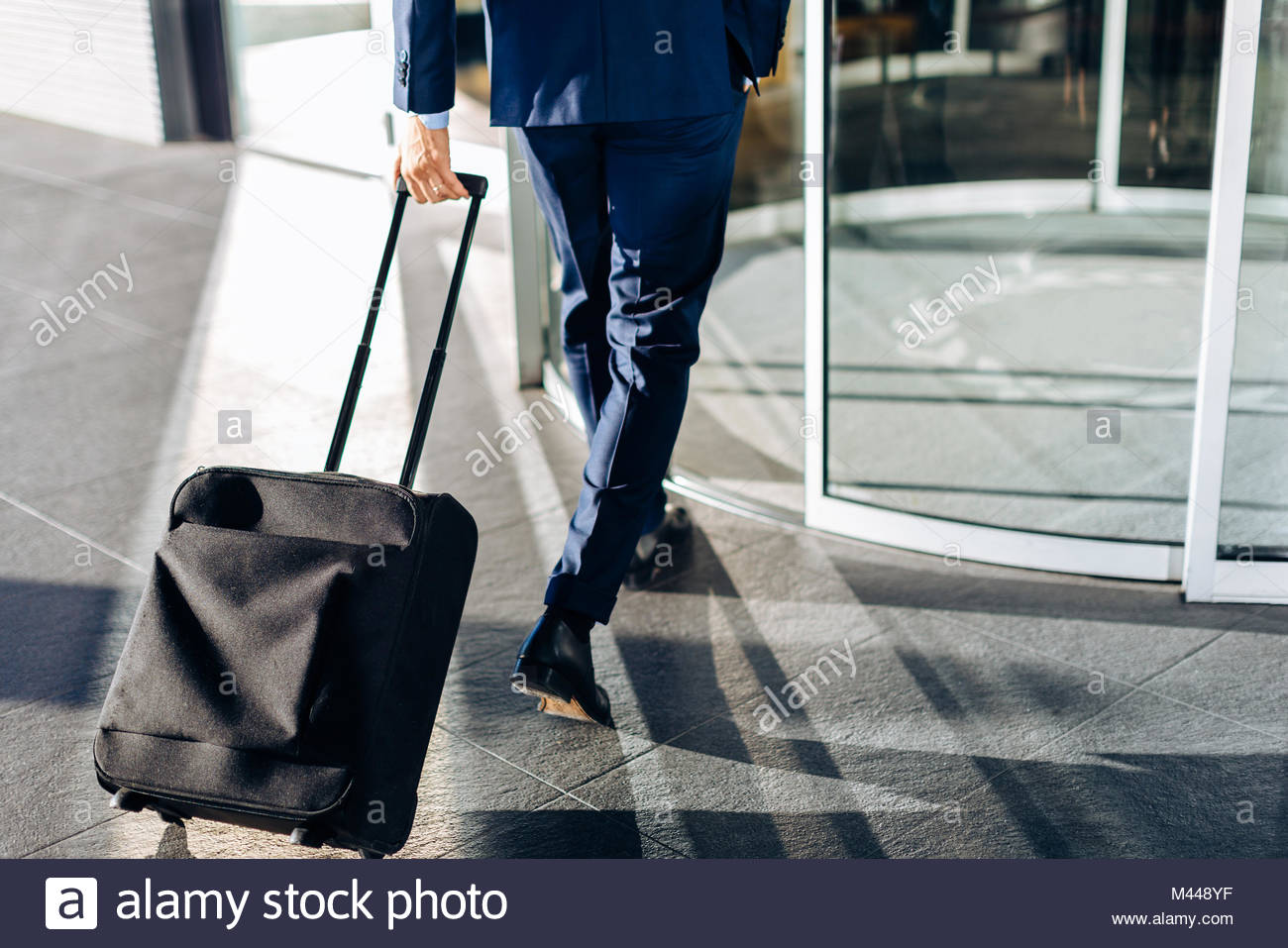 Businessman with wheeled luggage entering revolving doors of building - Stock Image