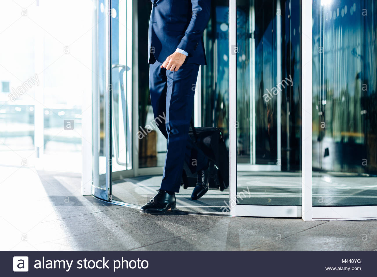 Businessman with wheeled luggage exiting revolving doors of building - Stock Image