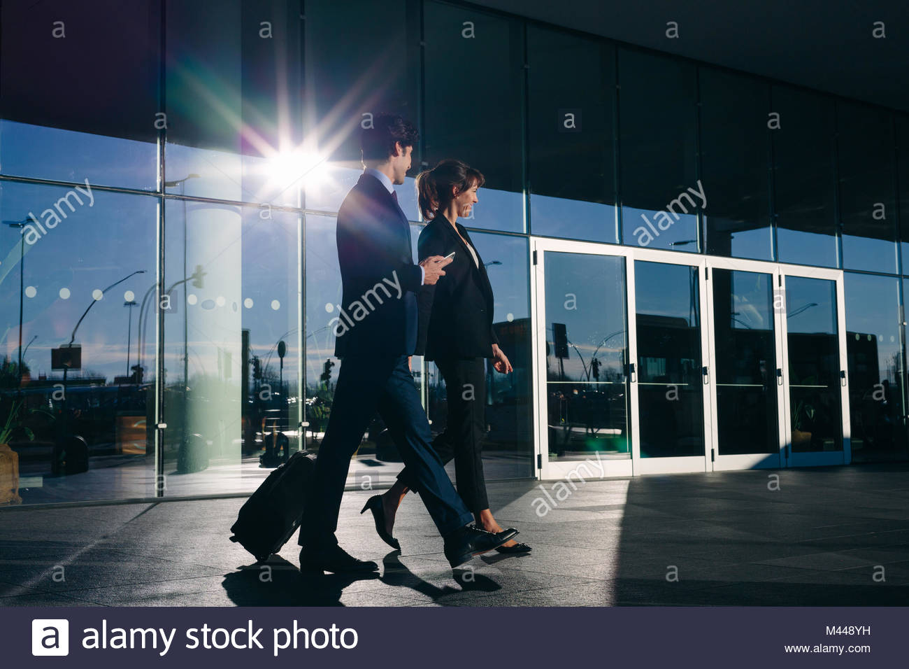 Businessman and businesswoman with wheeled luggage passing glass building, Malpensa, Milan - Stock Image
