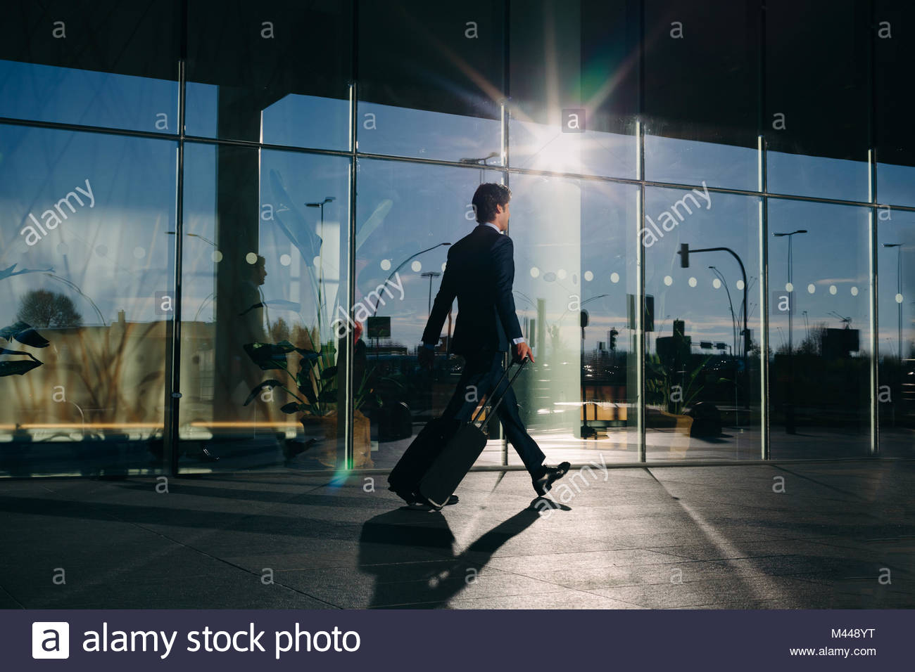 Businessman with wheeled luggage passing glass building, Malpensa, Milan - Stock Image