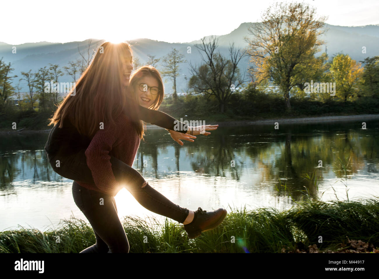 Young woman giving best friend piggy back on riverbank, Calolziocorte, Lombardy, Italy - Stock Image