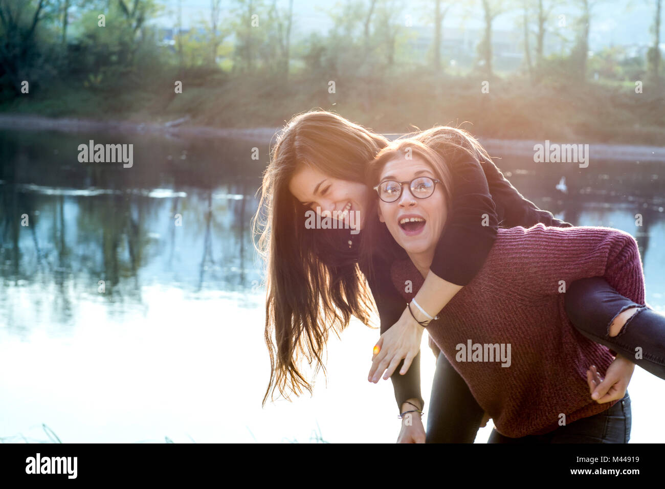 Young woman giving best friend piggy back by river, Calolziocorte, Lombardy, Italy - Stock Image