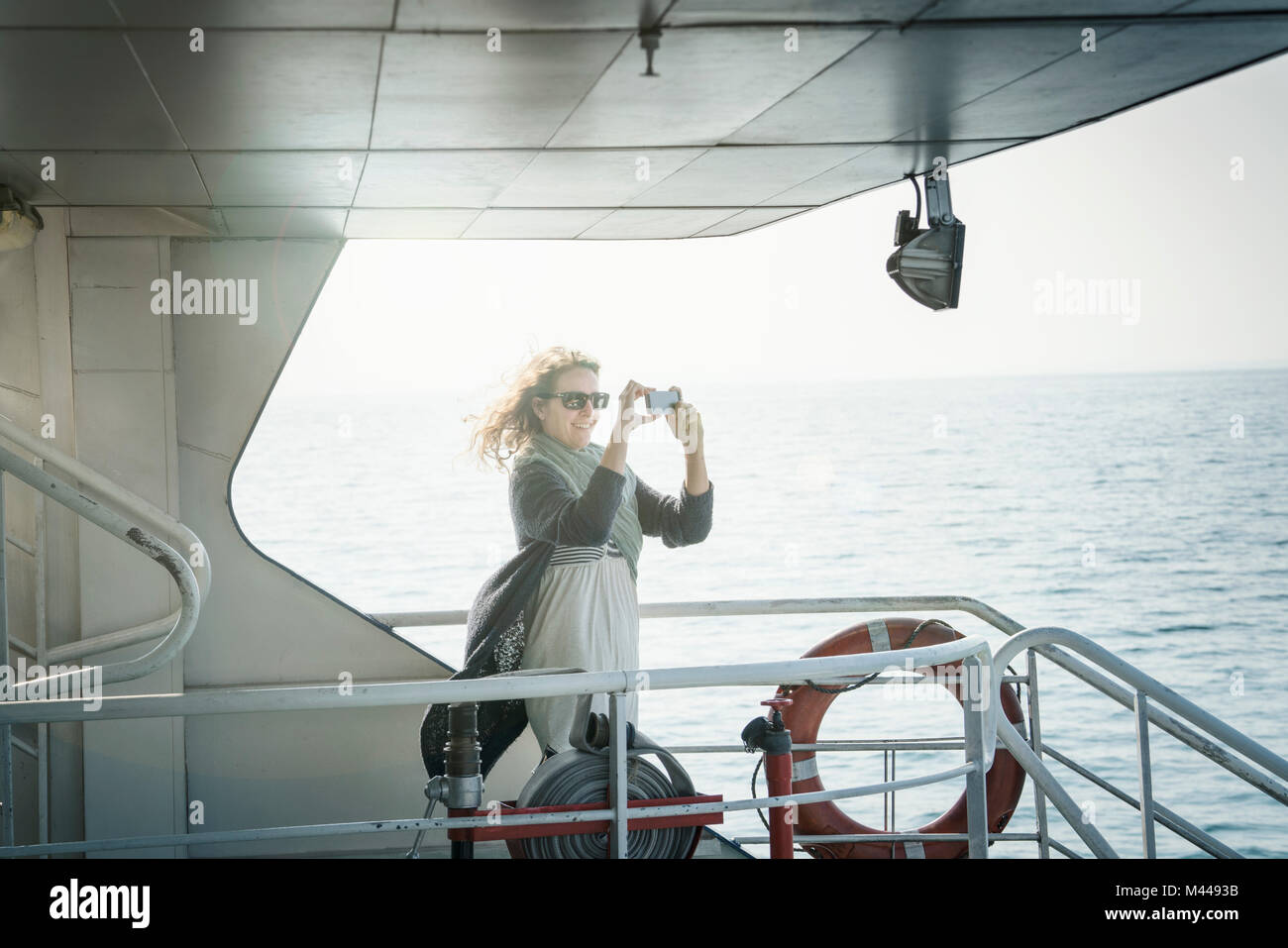Woman on ferry taking photograph Stock Photo