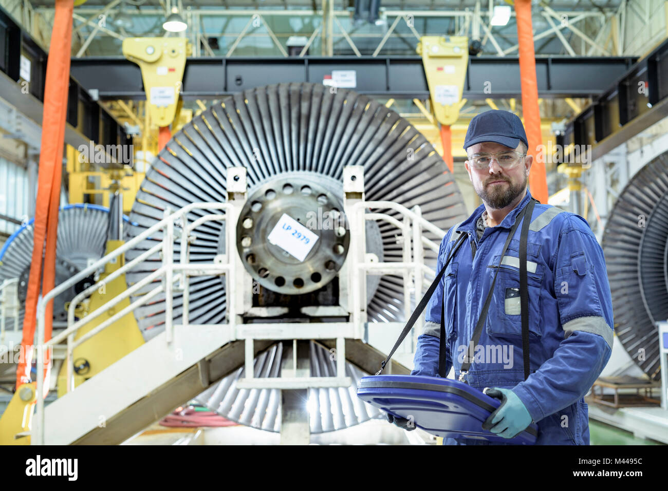 Crane operator with low pressure steam turbines in turbine maintenance factory - Stock Image