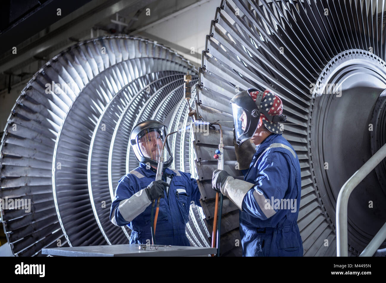 Engineers brazing ends of blades on low pressure steam turbine in turbine maintenance factory - Stock Image