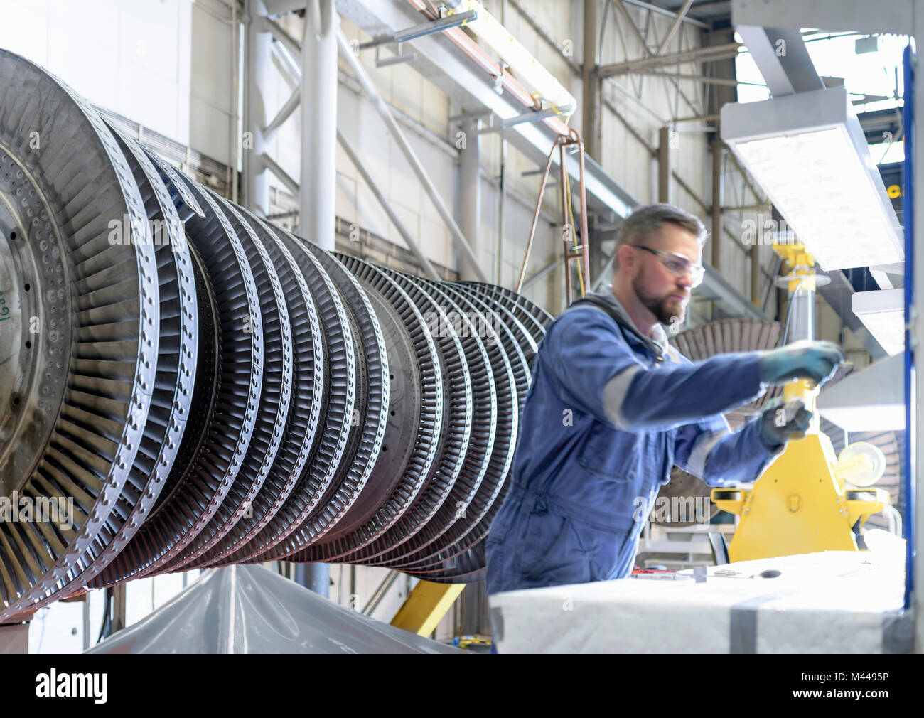 Engineer at workstation with high pressure steam turbine in turbine maintenance factory - Stock Image