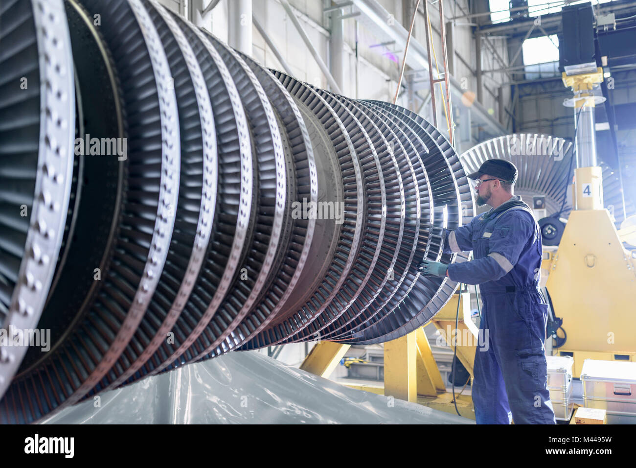 Engineer working on high pressure steam turbine in turbine maintenance factory - Stock Image