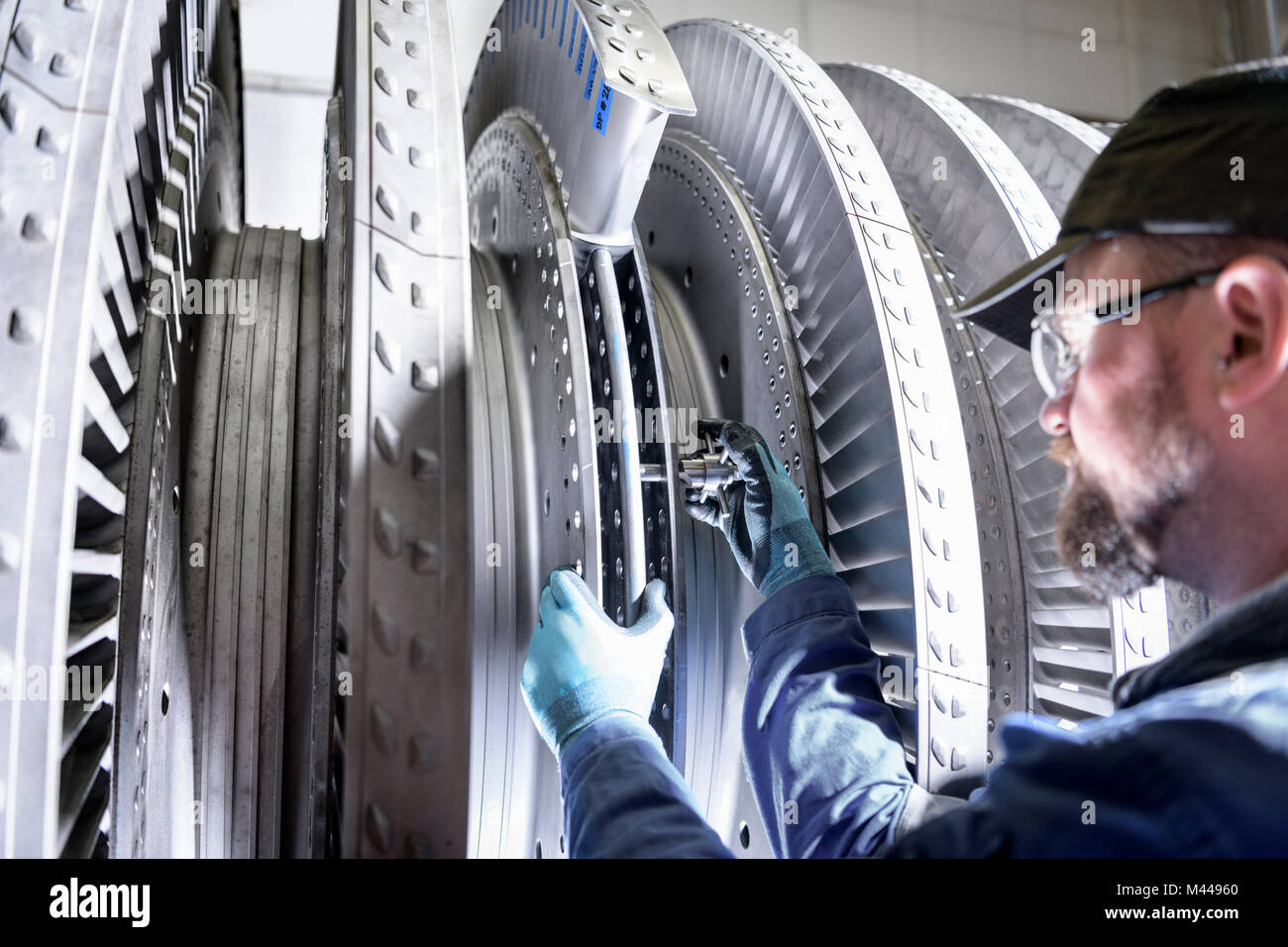 Close up of engineer working on high pressure steam turbine in turbine maintenance factory - Stock Image
