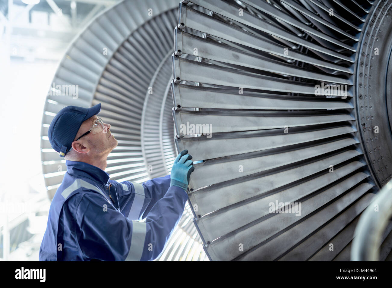 Close up of engineer inspecting low pressure turbine during inspection in turbine maintenance factory - Stock Image