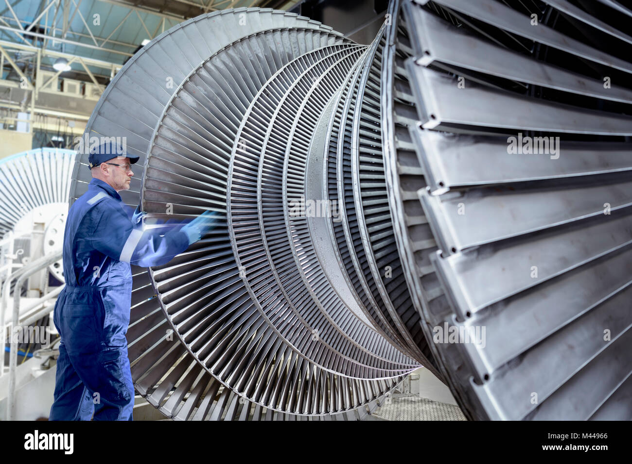 Engineer turning low pressure steam turbine during inspection in turbine maintenance factory - Stock Image