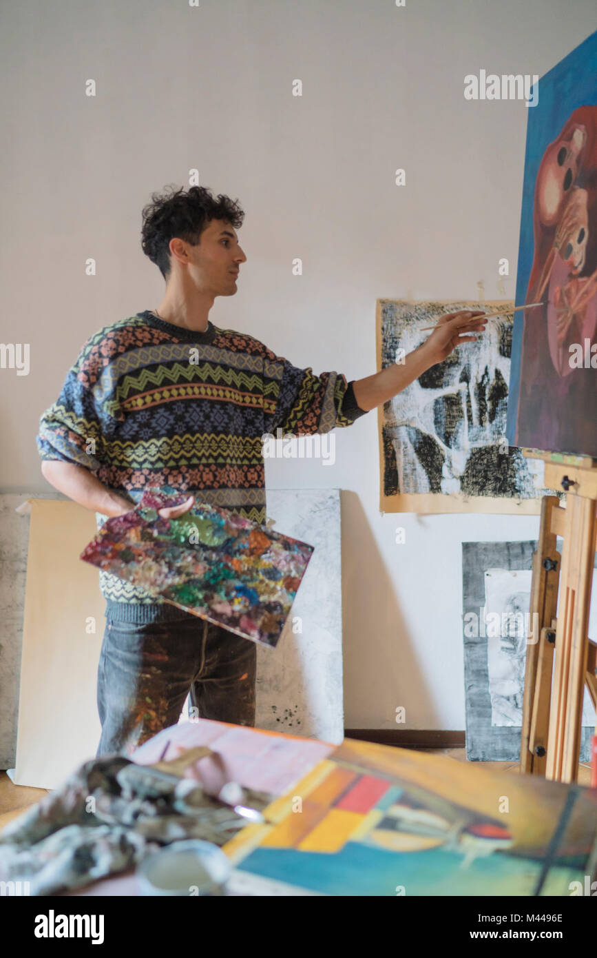 Male artist painting canvas in artists studio - Stock Image