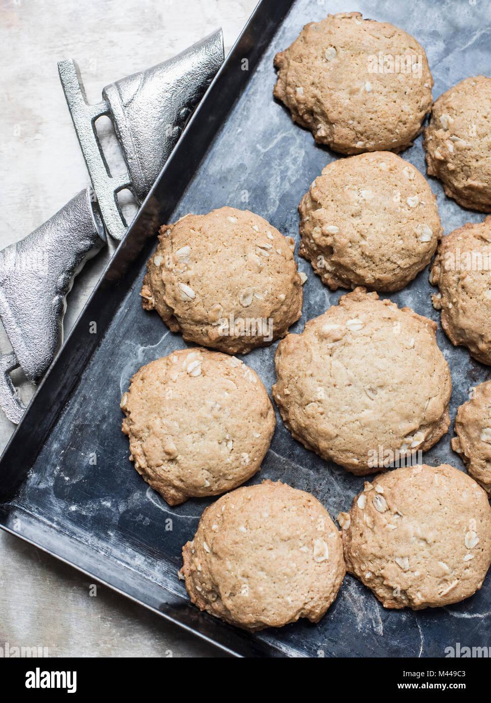 Freshly baked oatmeal cookies on baking pan - Stock Image