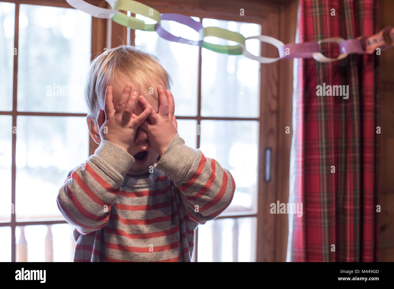 Boy playing hide and seek - Stock Image