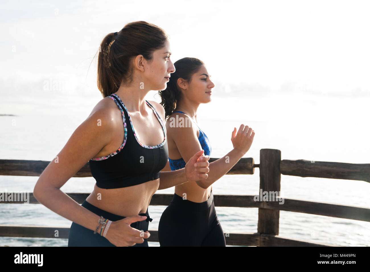 Two young female runners running on sea waterfront, Las Palmas, Canary Islands, Spain - Stock Image