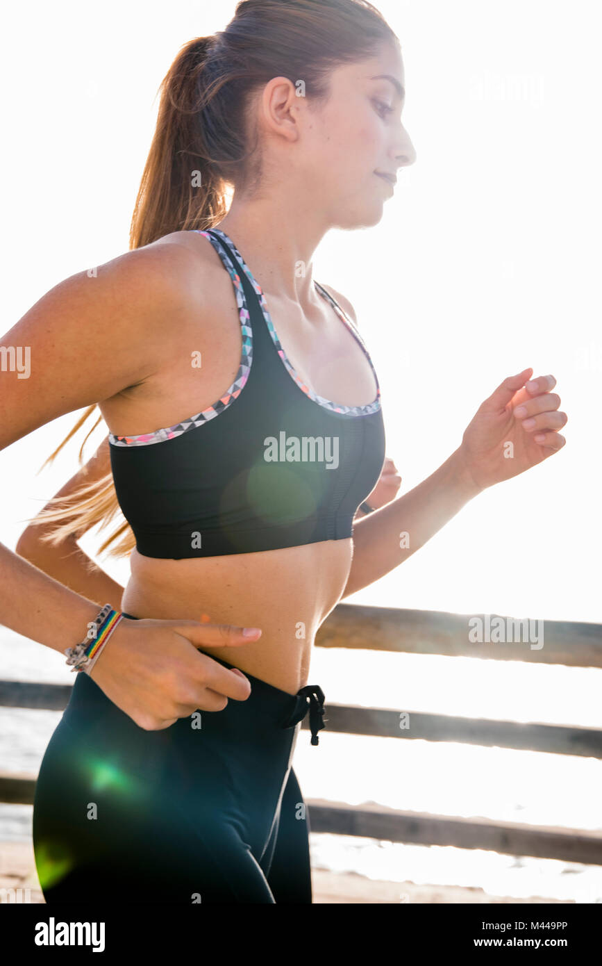 Two young female runners running on sea waterfront - Stock Image