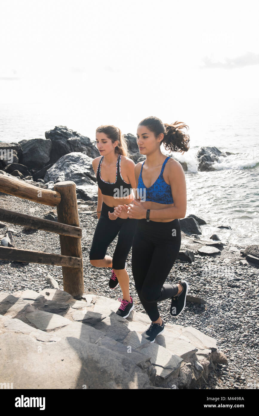 Two young female runners running up beach stairway, Las Palmas, Canary Islands, Spain - Stock Image
