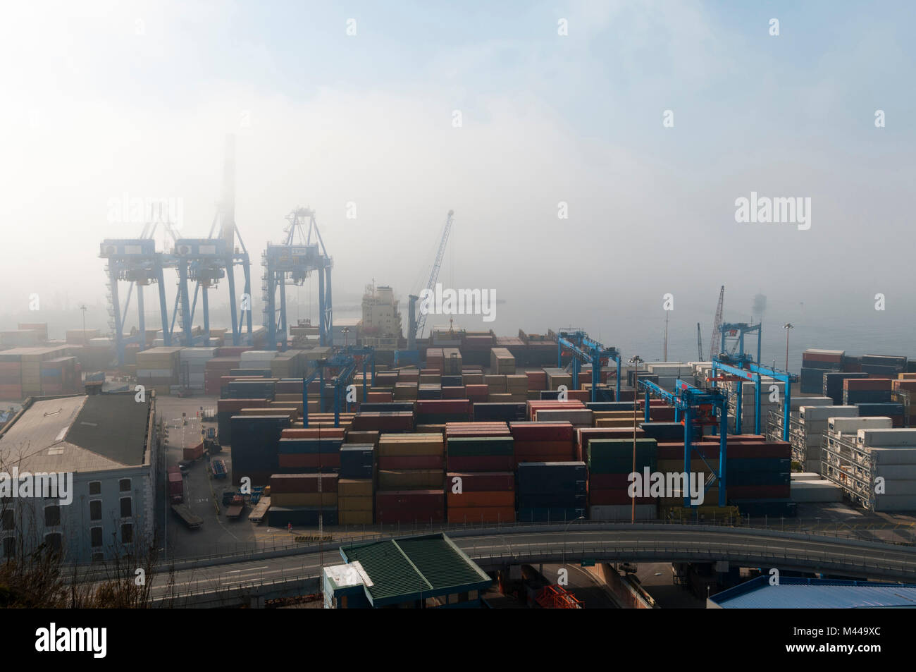 Shipping containers and harbour cranes in mist, Valparaiso, Chile Stock Photo