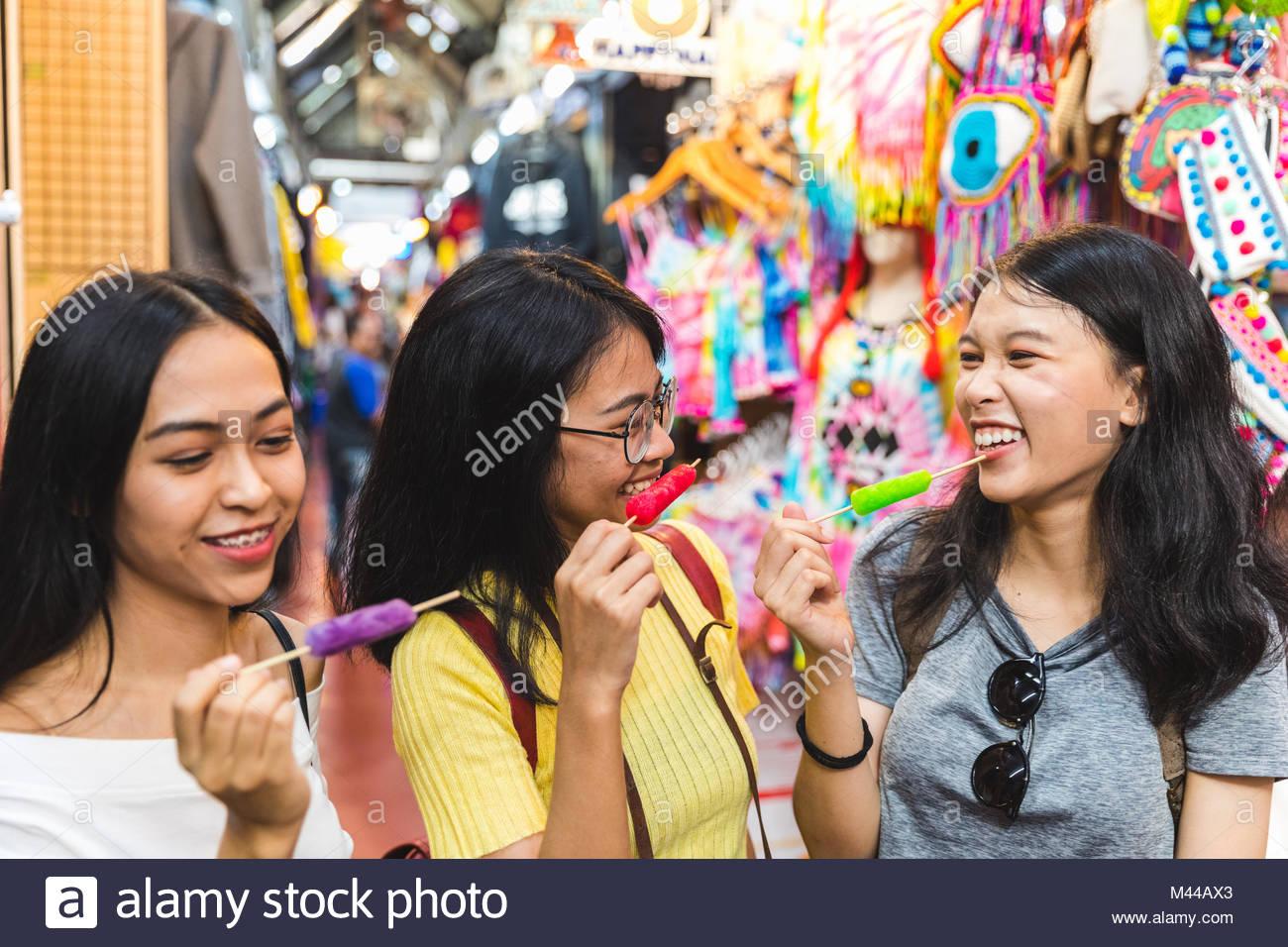 Happy young women with ice lollies in bazaar, Bangkok, Thailand Stock Photo