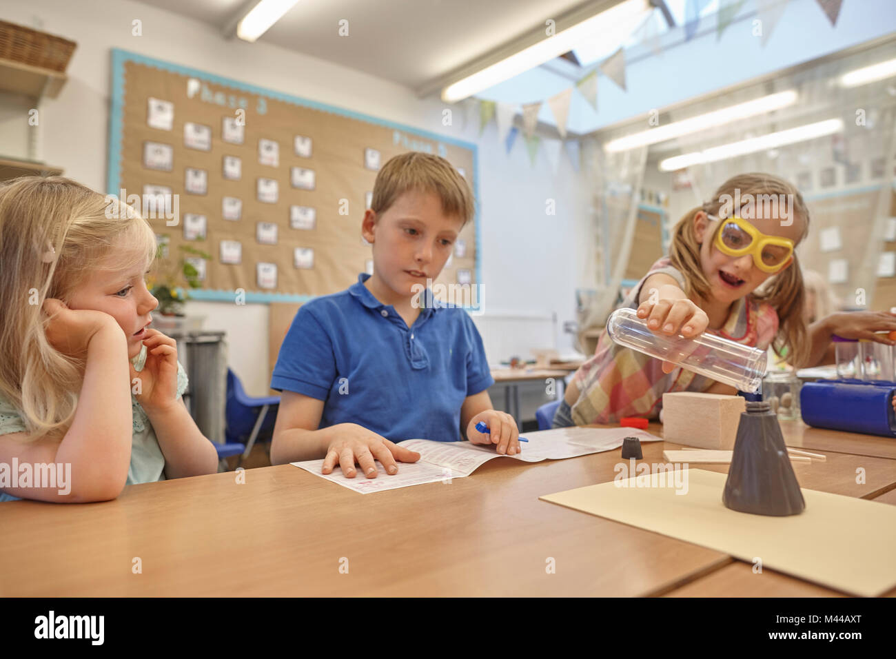 Primary schoolgirls and boy doing experiment at classroom desk - Stock Image