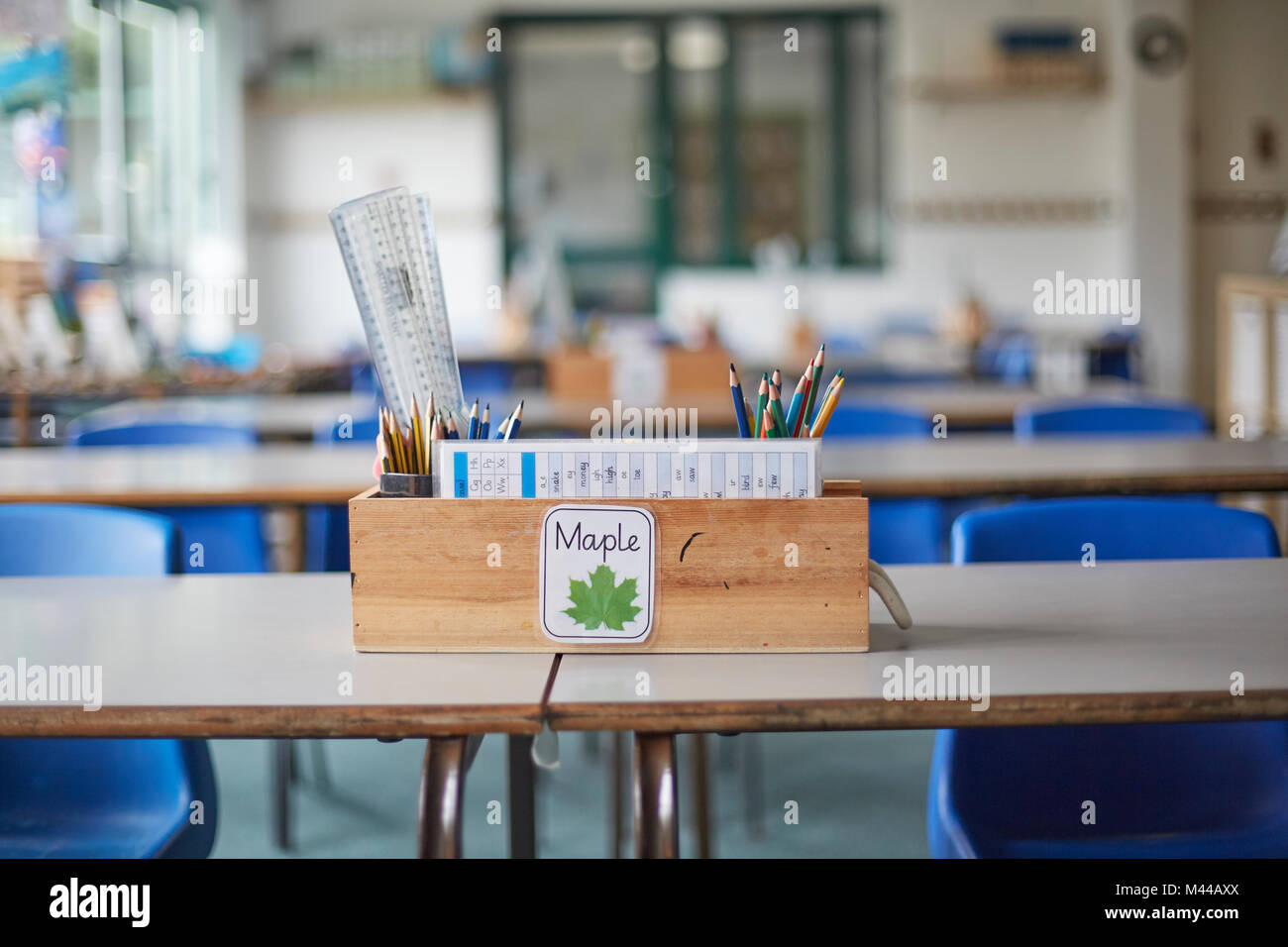 Classroom desk with wooden box full of pencils and rulers in primary school classroom - Stock Image
