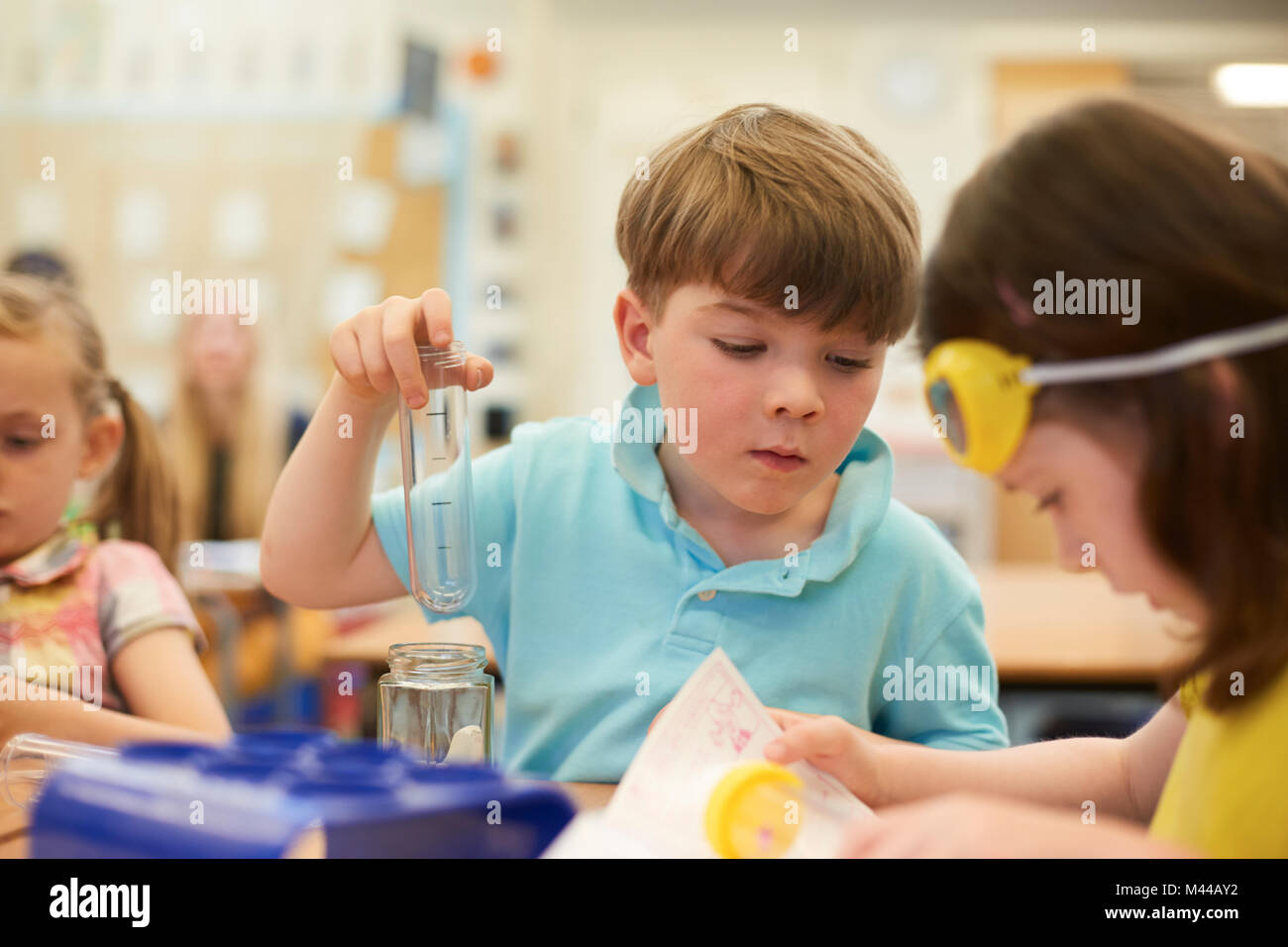 Primary schoolboy and girls doing test tube experiment in classroom - Stock Image