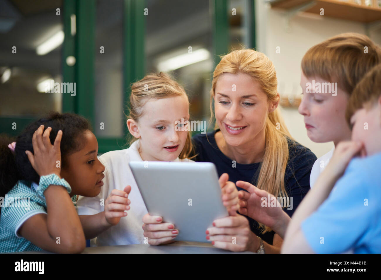 Teacher with schoolboys and girls looking at digital tablet in classroom at primary school - Stock Image