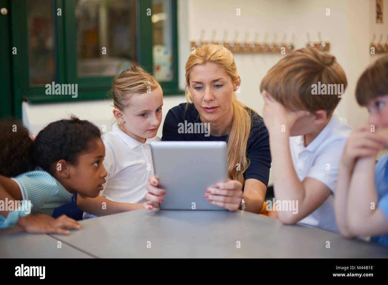 Teacher with schoolgirls and boys looking at digital tablet in classroom at primary school - Stock Image