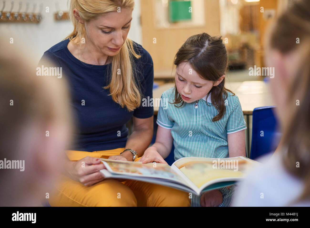 Teacher with schoolgirls reading storybook in classroom at primary school - Stock Image