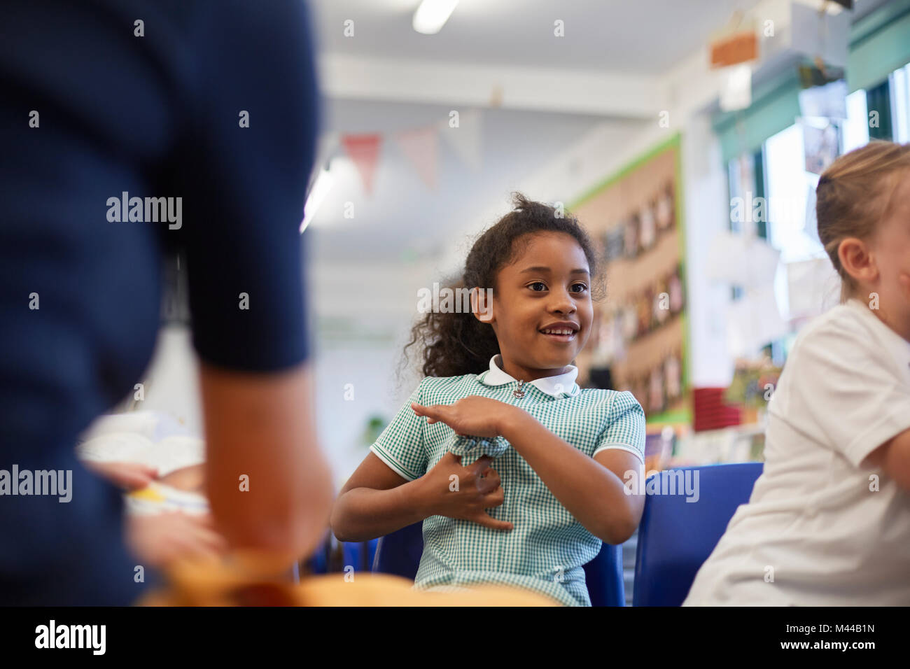 Schoolgirls and teacher in class at primary school, cropped - Stock Image