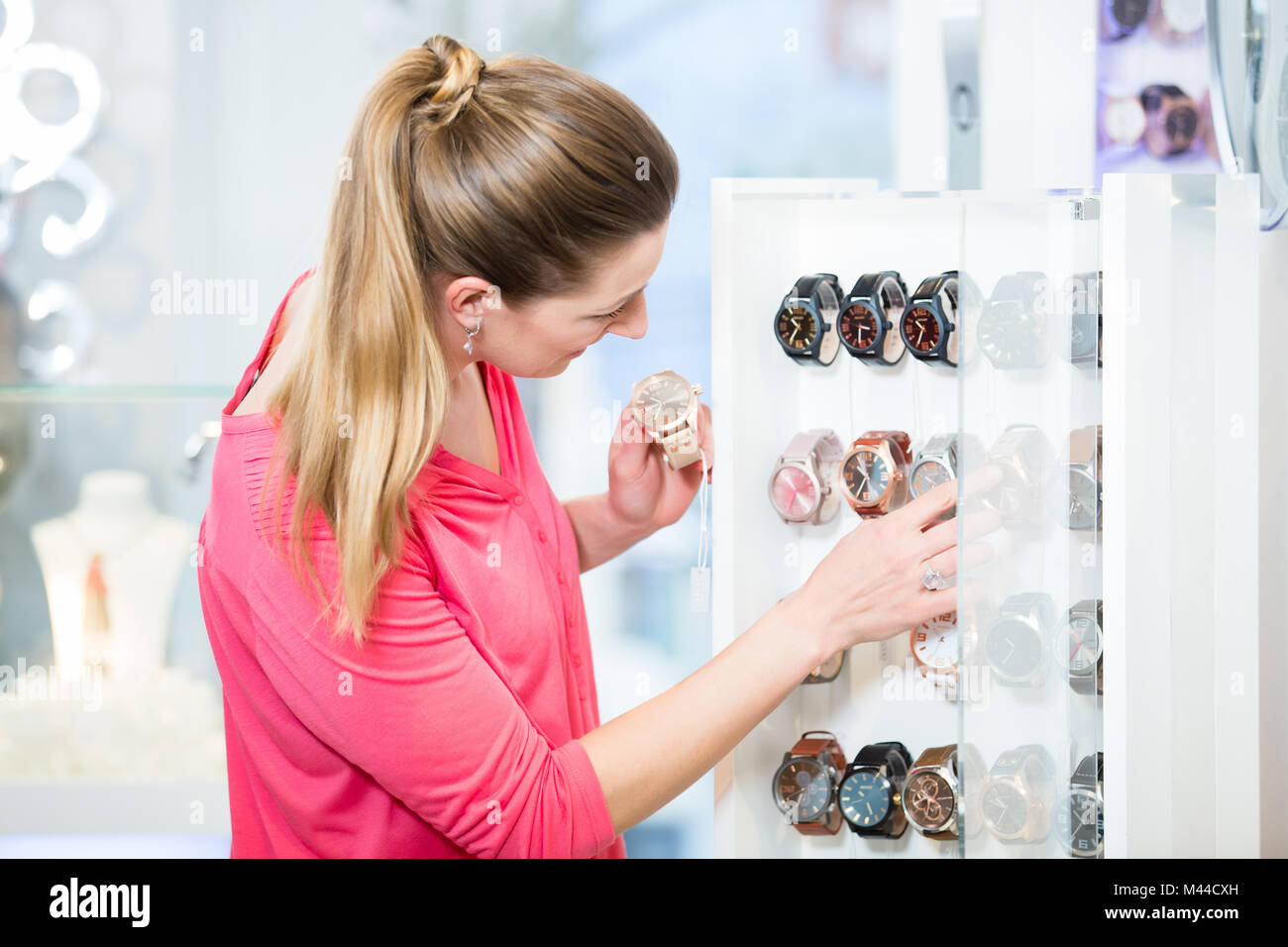 Female customer in store looking for wristwatches - Stock Image