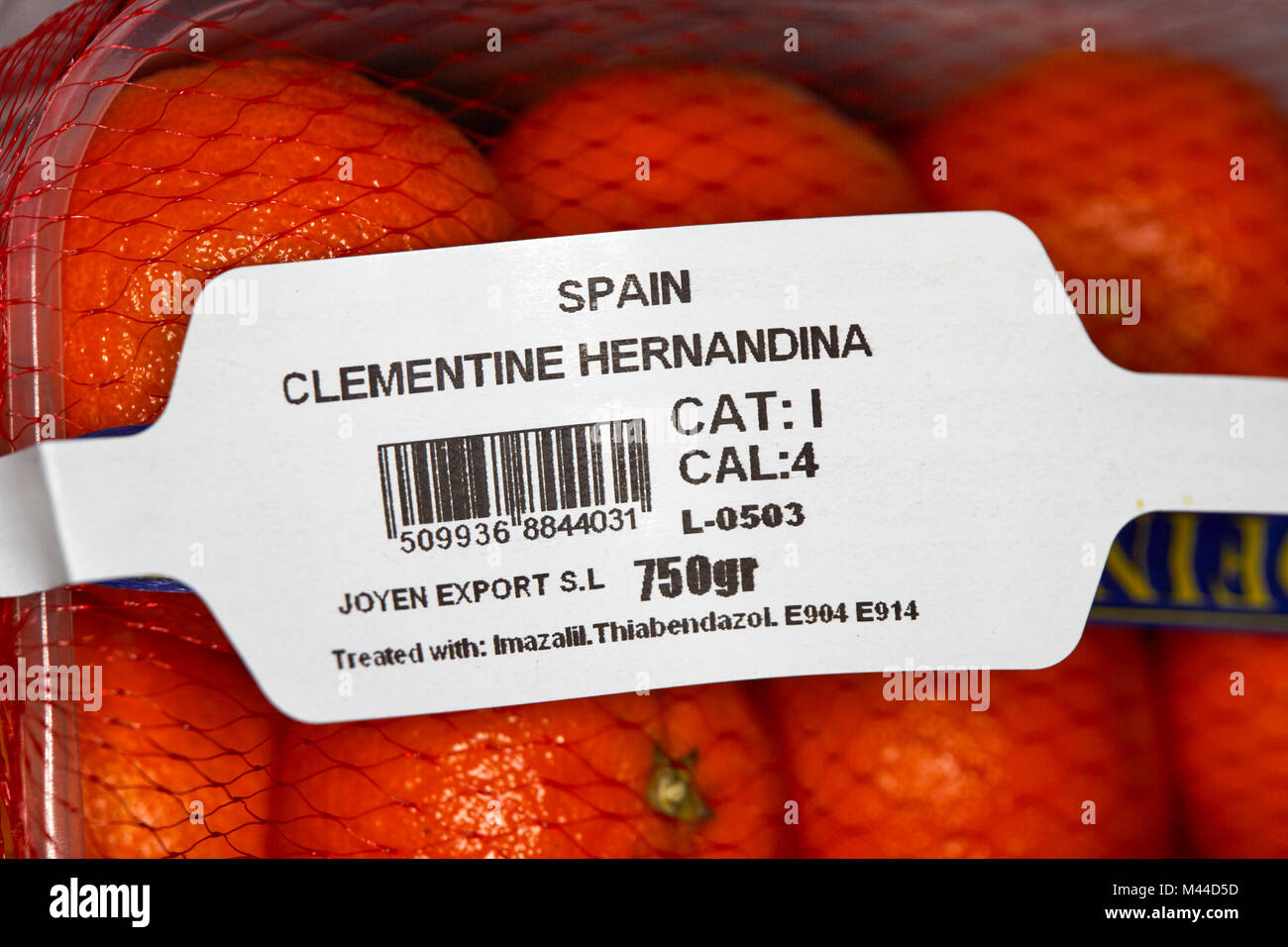 label on a box of spanish imported clementines in plastic packaging treated with pesticides - Stock Image