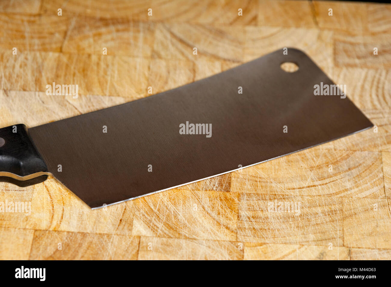 chinese cleaver knife sitting on a wooden butchers block - Stock Image