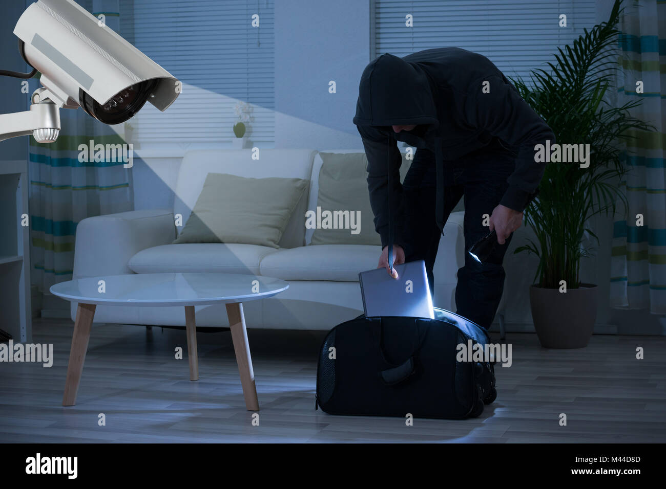 CCTV Camera Showing A Burglar Stealing Things In The House At Night - Stock Image