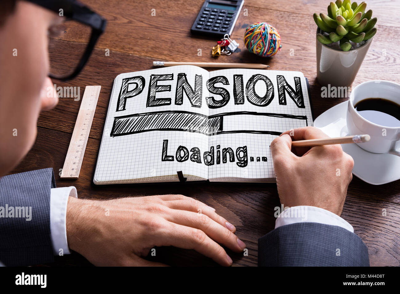 Close-up Of A Businessperson Drawing Loading Pension Concept On Notebook Over The Desk - Stock Image