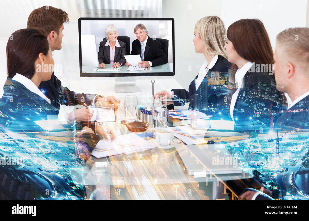 Double exposure of multiethnic business people having conference call with partners over illuminated city background - Stock Image