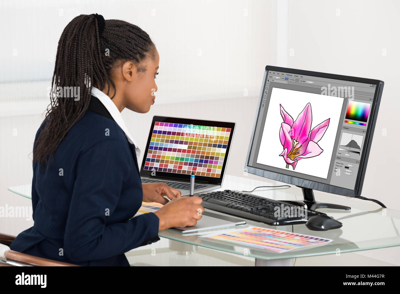 Female designer drawing flower on computer using graphic tablet at desk in office - Stock Image