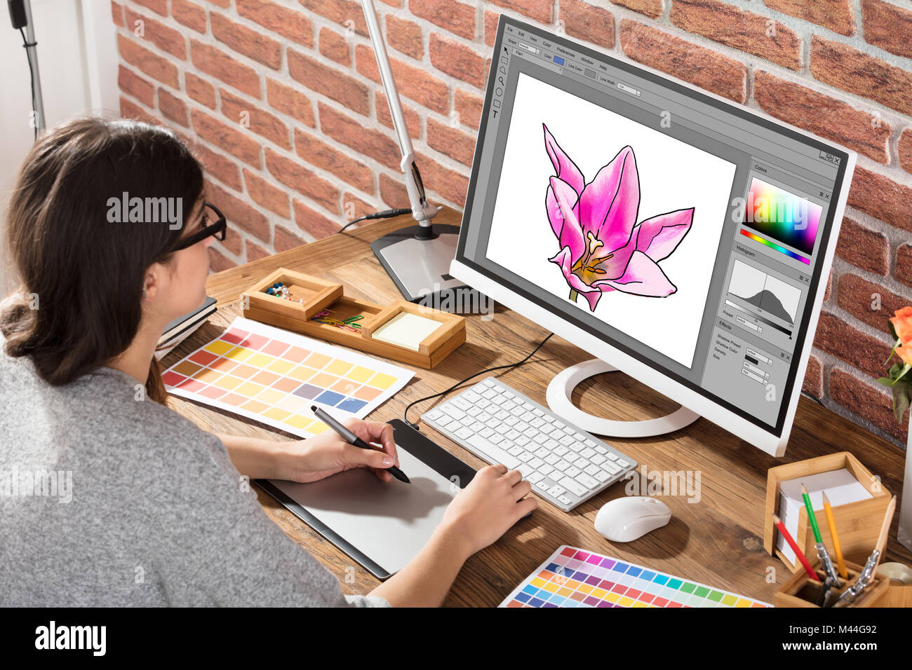 High angle view of female designer drawing flower on computer using graphic tablet in office - Stock Image
