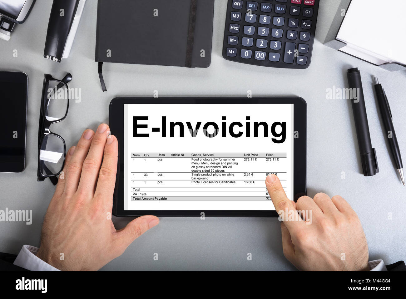 Directly above shot of businessman's hands going through e-invoicing on digital tablet in office Stock Photo