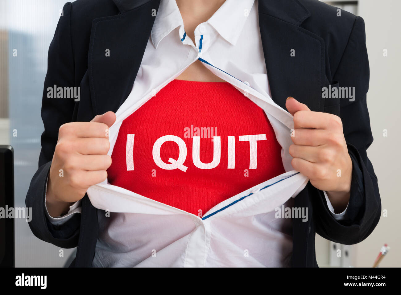 Midsection of businesswoman tearing off shirt with I Quit sign - Stock Image