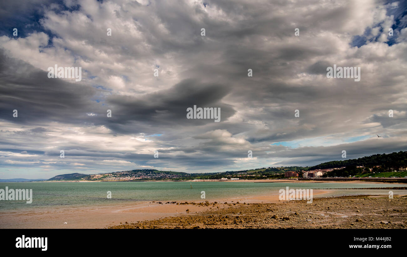 Clouds and sunshine at Colwyn Bay beach, North Wales - Stock Image