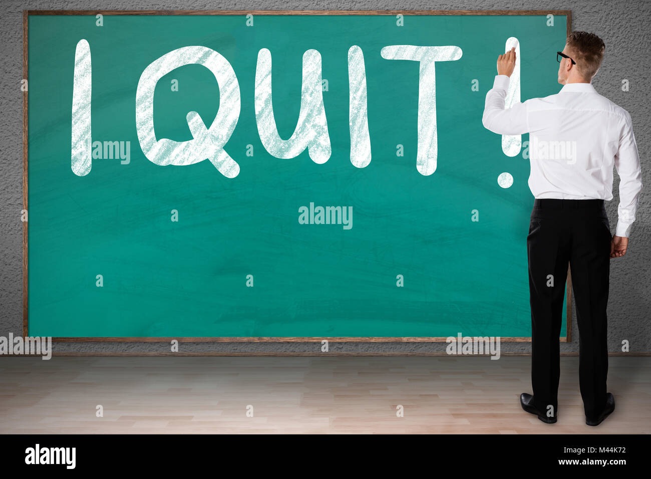 Full length rear view of businessman writing I Quit on blackboard - Stock Image