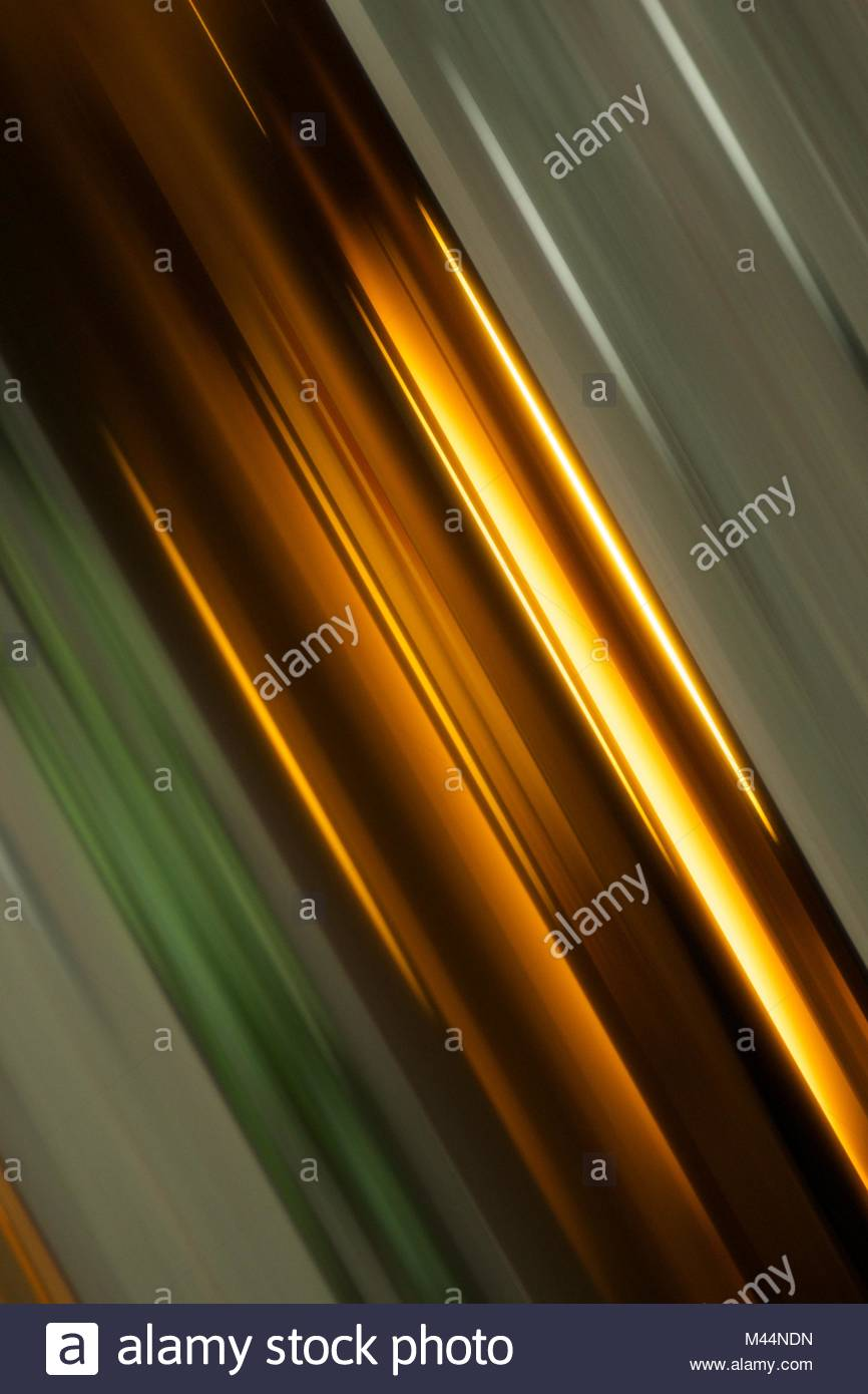 Abstract angled streaks of green and gold - Stock Image