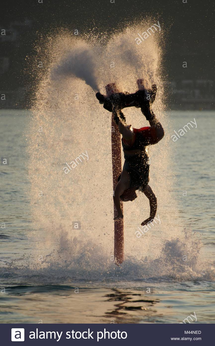 Flyboarder diving amid spray after back flip - Stock Image
