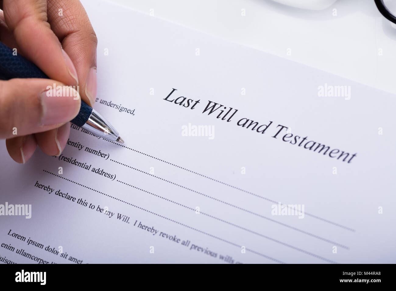 Close-up Of A Person's Hand Filling Last Will And Testament Form Stock Photo