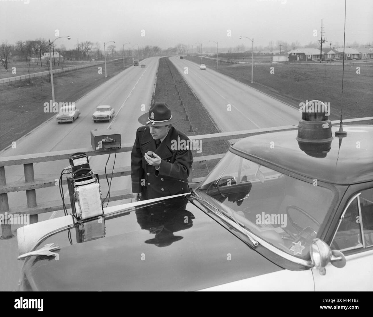 Policeman uses the new technology of radar to catch speeders on the Edens Expressway in Chicago, ca. 1960. - Stock Image