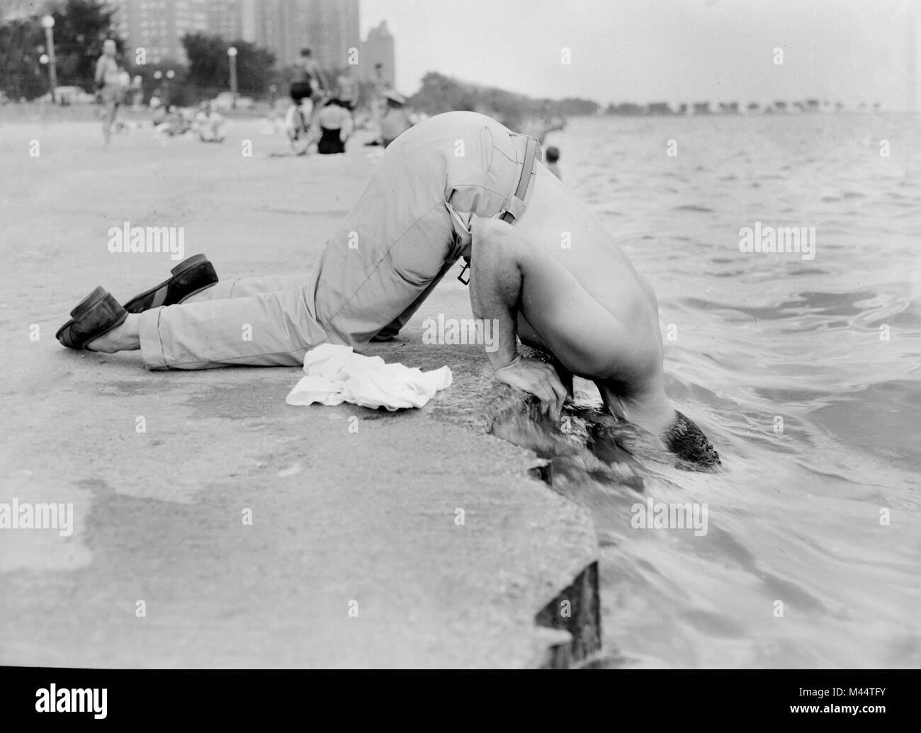 A man cools off along Oak Street beach in Chicago by sticking his head in Lake MIchigan, ca. 1955. - Stock Image