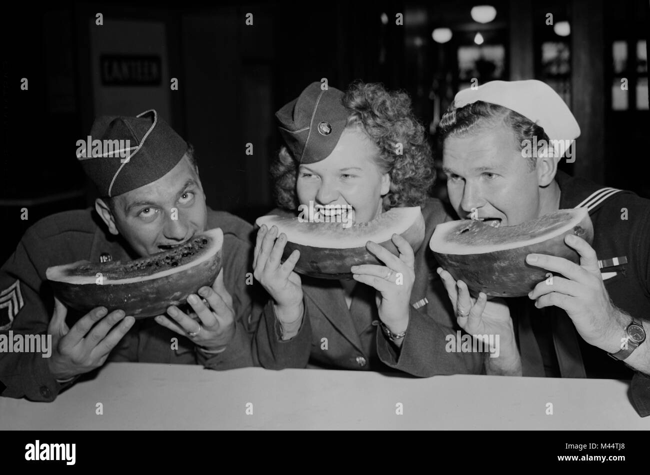 Three U.S. service members chow down on some watermelon, ca. 1945. - Stock Image