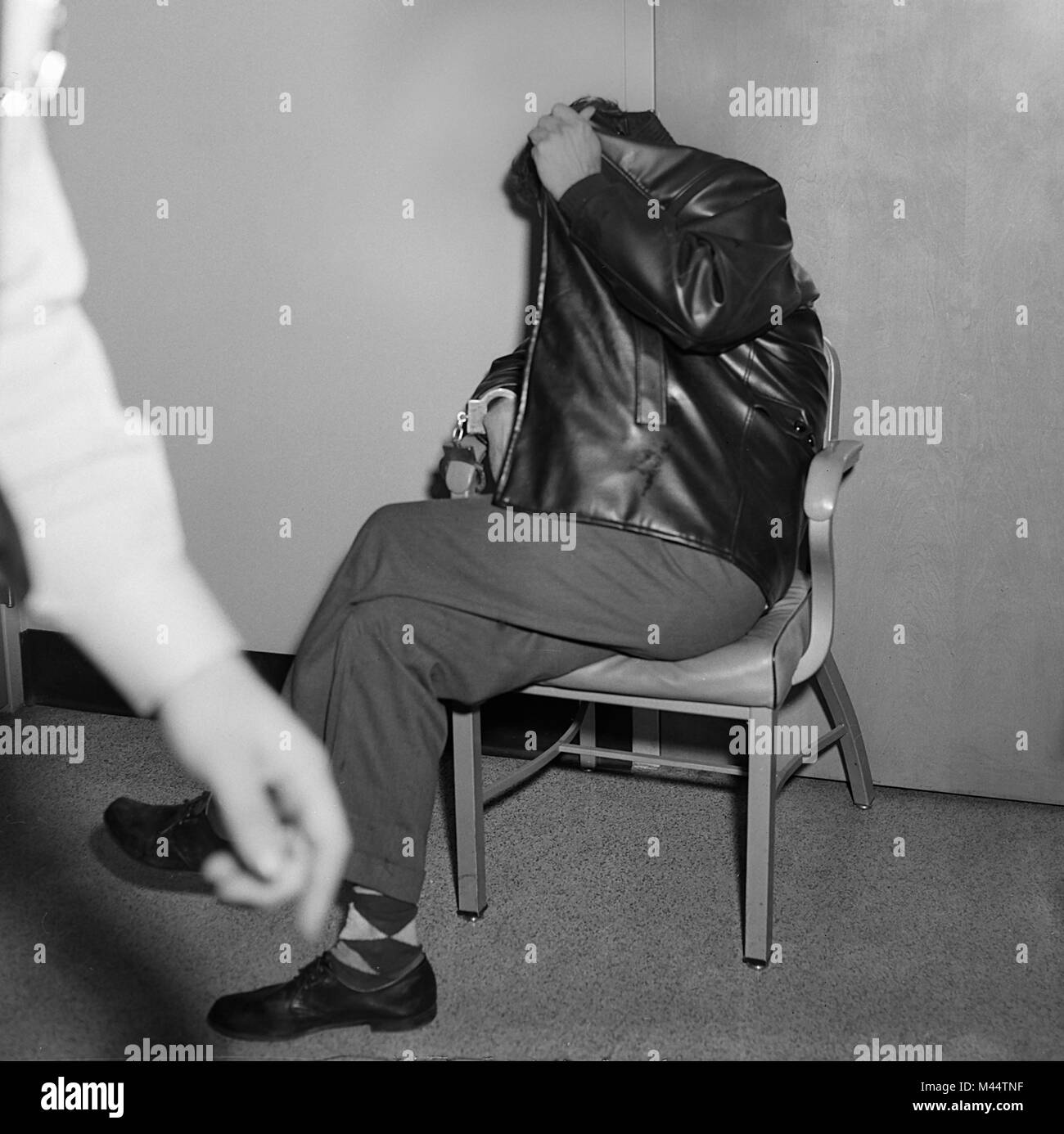 Handcuffed crime suspect covers up and hides from having his photo taken, ca. 1948. - Stock Image