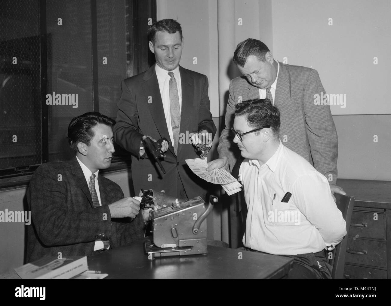 A suspected Chicago check forger is confronted by multiple cops with evidence of his crime, ca. 1950. - Stock Image